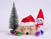 Toy dog ​​in a Christmas hat with a snowman Christmas tree b Royalty Free Stock Photography