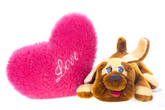 Toy dog and heart-shaped pillow Stock Photos