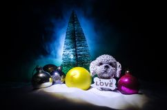 Toy dog - a symbol of the new year under the snow against the background of fir branches. Toy's dog as a symbol of 2018 New Year stock photo