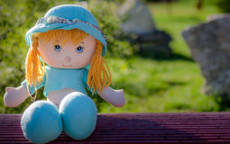 Toy doll. On a bench shot in natural light Royalty Free Stock Photography