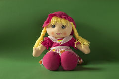 Toy doll. Pink dressed doll on a green background Stock Photo
