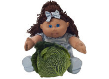 Toy doll sitting behind a cabbage Royalty Free Stock Photos