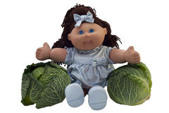 Toy doll sitting between two cabbages Royalty Free Stock Image