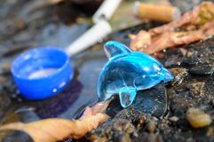 A toy dolphin in a puddle with garbage. Royalty Free Stock Photo