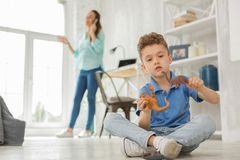 Amusing boy playing with toy dragons near mother. Toy dragons. Amusing handsome boy feeling very good while playing with toy dragons near mother talking by phone stock photo