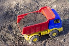 Toy dump truck stands on the ground full of sand royalty free stock images
