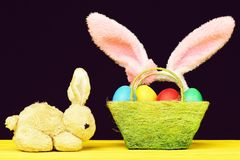 Toy Easter bunny and basket full of coloured easter eggs. Toy Easter bunny and green basket full of coloured easter eggs and pink fluffy rabbit ears hoop on stock photo
