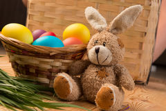 Toy easter bunny and colored eggs in a basket Stock Photos