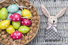 Toy Easter bunny, colorful eggs in basket on wicker background Royalty Free Stock Photo