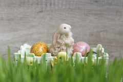 Toy easter bunny with eggs sitting in basket on green grass stock photo