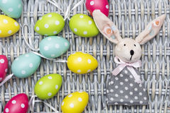 Toy Easter dressed bunny, colorful dyed eggs on wicker background Royalty Free Stock Photos
