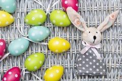 Toy Easter gekleed konijntje, kleurrijke geverfte eieren op rieten achtergrond Royalty-vrije Stock Foto's