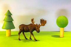 Toy elk in a toy forest. like a real moose on a bright studio background with wooden trees. Eco toys. stock images