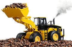 Toy excavator loads the coffee beans Stock Photos
