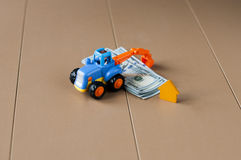 Toy excavator rakes dollars. Toy excavator with dollars and small wooden house Royalty Free Stock Image
