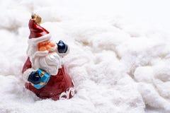 Toy Father Christmas que se coloca en algodón de la nieve Foto de archivo