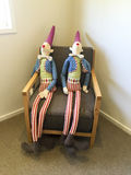 Toy figures sitting on chair Royalty Free Stock Images