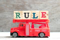 Toy fire ladder truck hold block in word rule on wood background stock images
