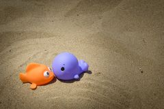 Toy fish kiss on sand royalty free stock image