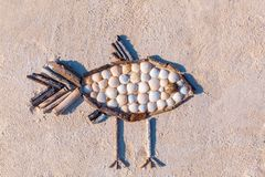 Toy fish made of sea shells on sand stock photography