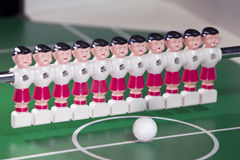 Toy football players stand in the field in a row and a ball in the center Stock Photos