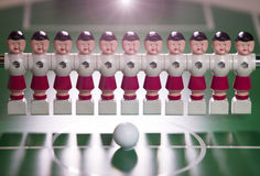 Toy football players stand in the field in a row and a ball in the center Royalty Free Stock Images