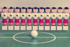 Toy football players stand in the field in a row and a ball in the center, retro effect Stock Photos
