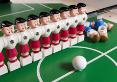 Toy football players stand on the football field, several figures have fallen, lie. Concept of excess, unnecessary people Royalty Free Stock Images