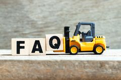 Free Toy Forklift Hold Block Q To Complete Word FAQ Abbreviation Of Frequently Asked Questions On Wood Background Stock Photos - 167163713