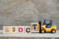 Toy forklift hold block T to word 23 oct on wood background Concept for calendar date in month October stock photography