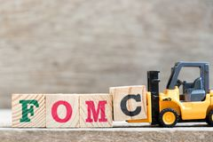 Toy forklift hold letter block c in word FOMC Federal Open Market Committee on wood background royalty free stock image