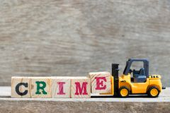 Toy forklift hold letter block E to complete word crime stock photos