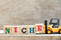 Toy forklift hold block E in word niche on wood background stock image