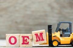 Toy forklift hold letter block M in word OEM abbreviation of original equipment manufacturer stock image