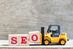 Toy forklift hold letter block O to word SEO abbreviation of Search Engine Optimization on wood background stock image