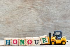 Toy forklift hold letter block r to word honour on wood background royalty free stock photo