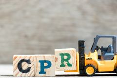 Toy forklift hold letter block R in word CPR abbreviation of Cardiopulmonary resuscitation. On wood background stock photography