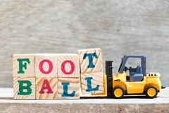 Toy forklift hold letter block T,L to word football on wood background royalty free stock photo