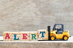 Toy forklift hold letter block T to word alert on wood background stock photo
