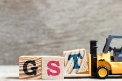 Toy forklift hold letter block T to word GST abbreviation of Goods and Services Tax on wood background royalty free stock photography