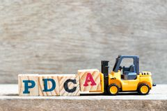 Toy forklift hold letter block A to complete word PDCA Plan, Do, Check, Act stock image