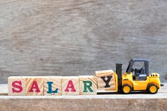 Toy forklift hold letter block Y to word salary on wood background royalty free stock photos