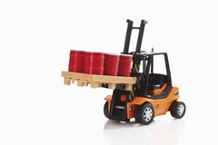 Toy forklift truck carrying barrels on white background Stock Photo