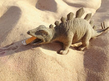 Toy in the form of a dinosaur standing on the sand eating butt of a cigarette. Royalty Free Stock Images