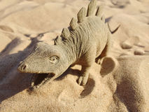 Toy in the form of a dinosaur standing on sand. Stock Image
