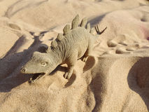 Toy in the form of a dinosaur standing on sand. Royalty Free Stock Image