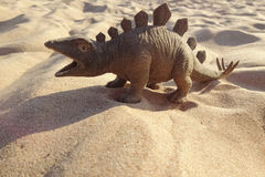 Toy in the form of a dinosaur standing on sand. Stock Photos