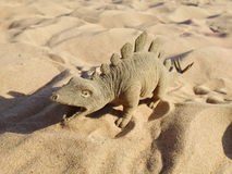 Toy in the form of a dinosaur standing on sand. Stock Images