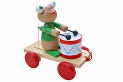Toy frog with drum. Wooden frog on the cart with red wheels Royalty Free Stock Photo