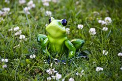 Toy frog sitting in the grass stock image